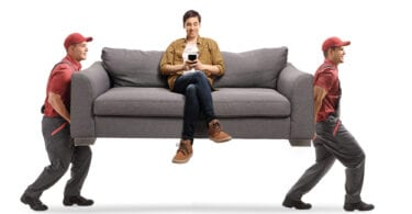 Movers carrying man on couch