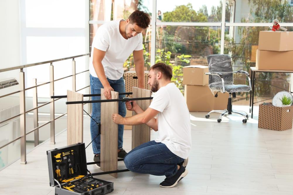 Two moving men taking apart a shelf