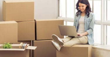 woman sitting on boxes searching on laptop