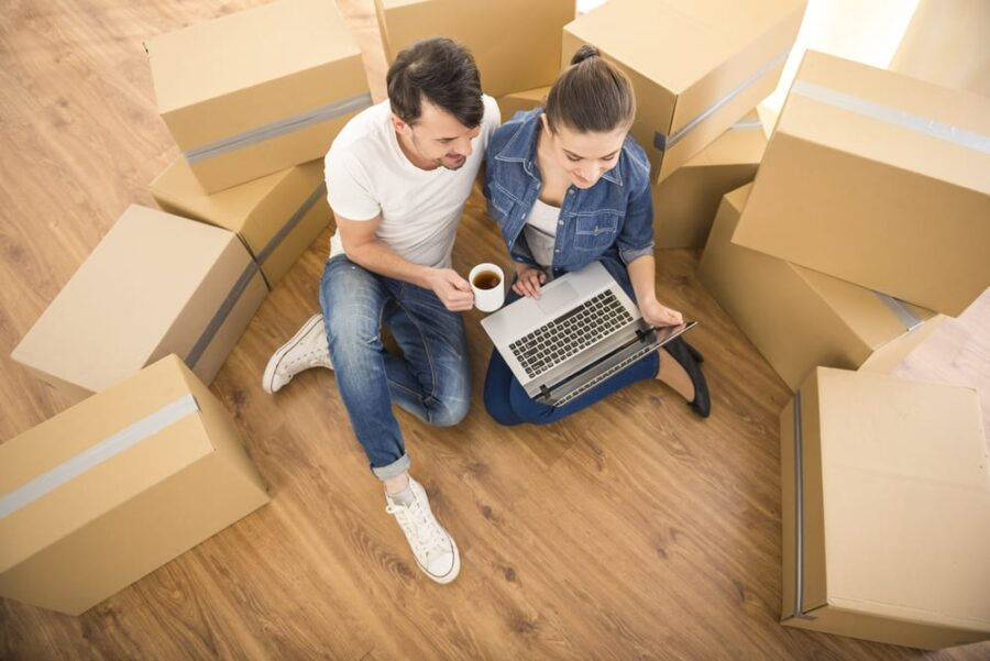 man and woman with laptop and moving boxes