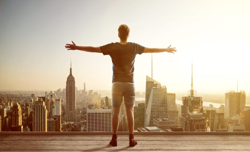man facing city skyline with arms outstretched