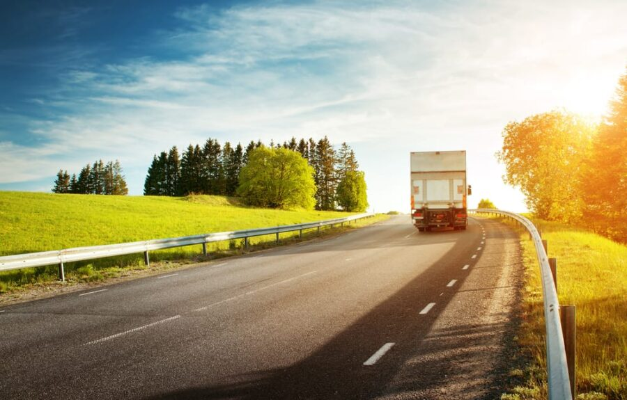 moving truck driving on sunny open road