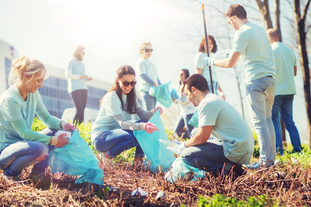 volunteers smiling and cleaning up a park