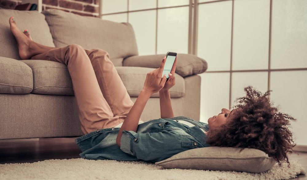 happy woman reclining using smartphone