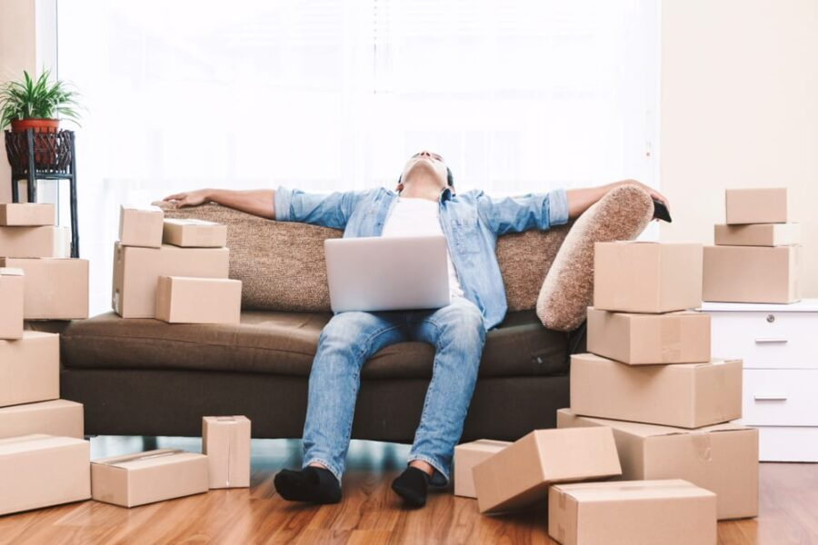 man on sofa with computer and boxes