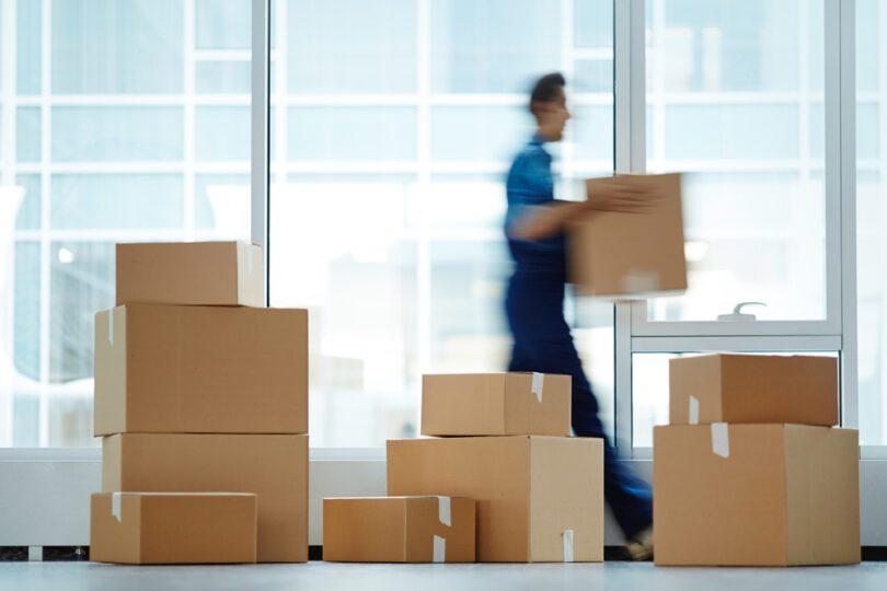 blurred man carrying box