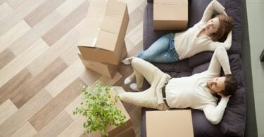 couple relaxing with moving boxes