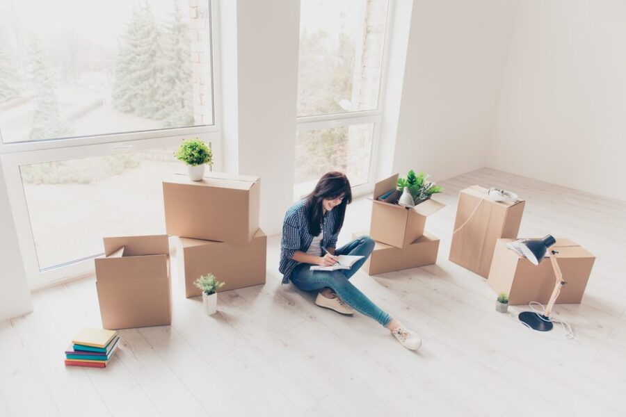 woman with boxes making list